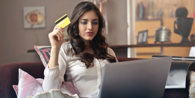 A young woman sitting in a living room has a laptop in front of her and a debit card in her hand