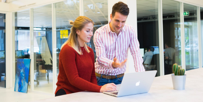 A man and a woman stand in front of a laptop in the middle of an open plan office
