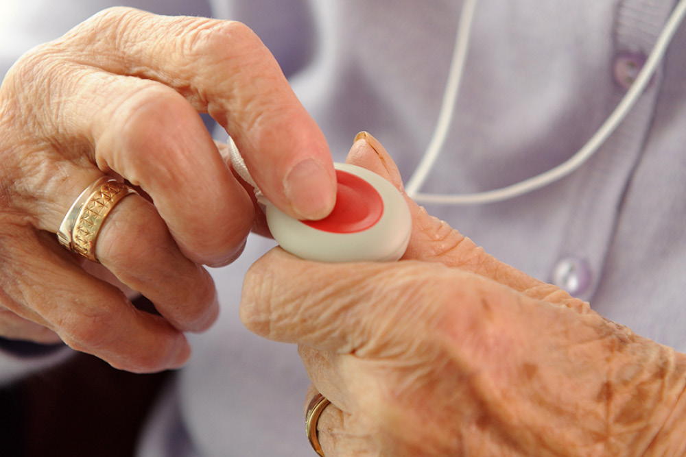 An older lady is holding a LifeLine pendant in both hands, with one finger on the red button