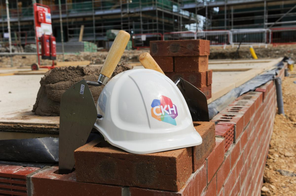 A hard hat with the CKH logo sits on a construction site