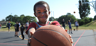 A young child is smiling and holding a basketball out in front of him