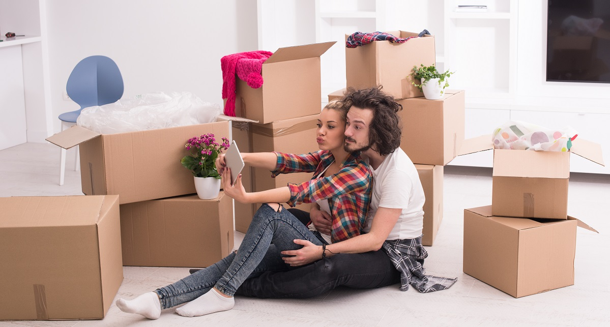 A man and a woman are sat on the floor surrounded by cardboard boxes in their new home