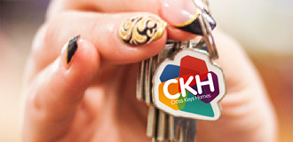 A hand is holding up keys with a Cross keys logo key ring in the front