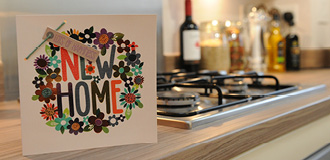 A new home card is standing on the kitchen counter by the stove