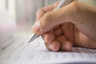 A hand is holding a pen over a form