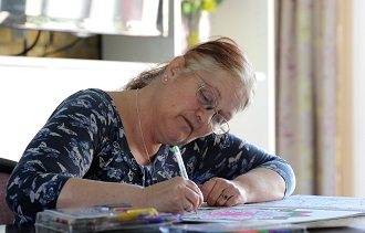 A woman is sat down colouring in at a table