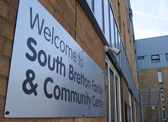 On the side of a building there is a Welcome to South Bretton Community Centre sign