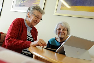 Two elderly ladies are sat smiling and looking at a laptop screen