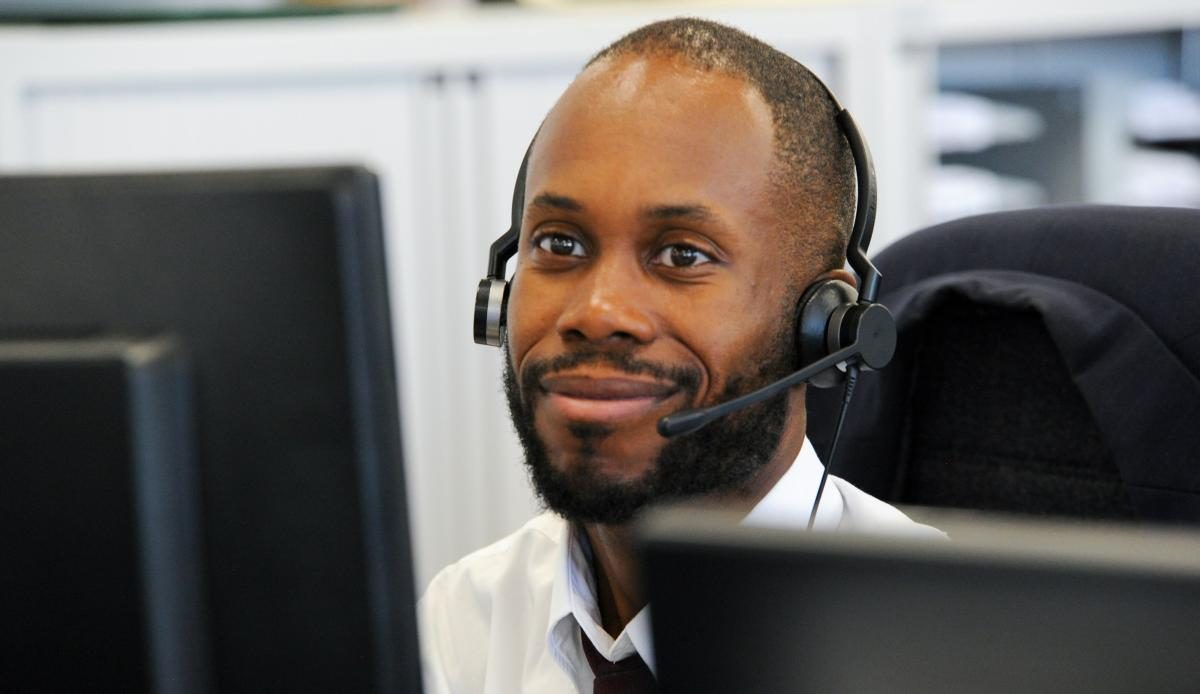 Image shows a CKH employee wearing a phone headset making calls
