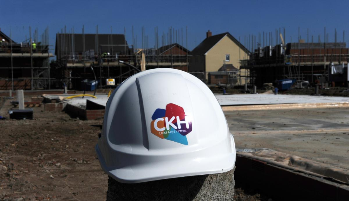 Image of a CKH branded hard hat with a building site in the background