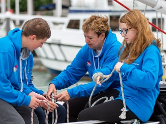 Two teenage students and a teacher tie knots on a sailing boat