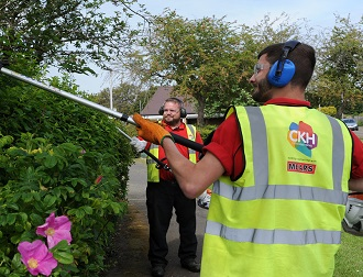 Two men wearing CKH and Mears branded PPE work on pruning brushes
