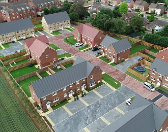 An aerial view photo of a new housing development showing red brick homes next to a green field