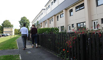Image shows two people walking down a road with homes to their right.