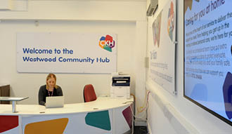 Image shows a woman working at the reception desk with a sign above saying 'Welcome to the Westwood Community Hub'