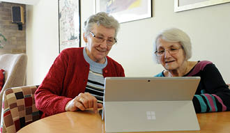 Image shows two women sat at a table looking at a computer and laughing