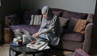 Image shows woman sitting on sofa working on laptop, with books on the coffee table