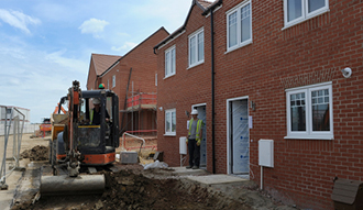 Image shows a mini digger working outside a partially finished house on a building site