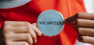 Image shows a badge pinned to a red jumper that says volunteer