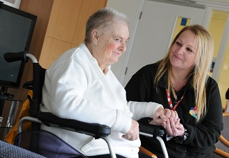 image-Scheme manager holding hand of resident in wheelchair - card.jpg