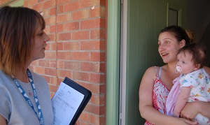 resident with baby talking to neighbourhood manager at front door - card.jpg