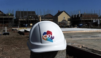 CKH hard hat in front of construction site - card.jpg
