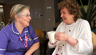 A CKH Care Worker speaks to a resident who is holding a mug and smiling